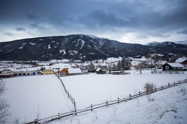 Piękny krajobraz austriackiego miasta w dolinie w alpach pokrytych śniegiem