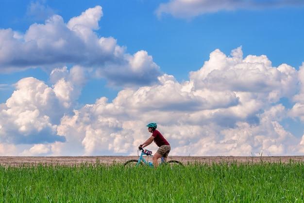Piękny krajobraz dziewczyny na rowerze w zielonym polu
