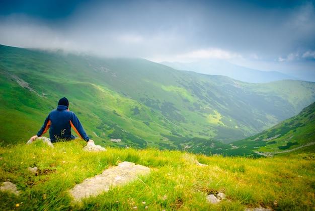 Piękny krajobraz górski z jeziorem i chmurami w karpatach i wyglądem człowieka