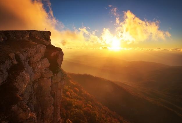 Piękny krajobraz górski z nieba słońca w okresie jesiennym. fotograf robi zdjęcia na szczycie góry