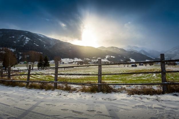 Piękny krajobraz górskiej farmy w austriackich alpach o zachodzie słońca
