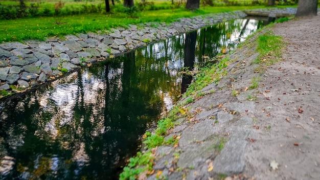 Piękny krajobraz kanału wodnego przepływającego przez jesienny park