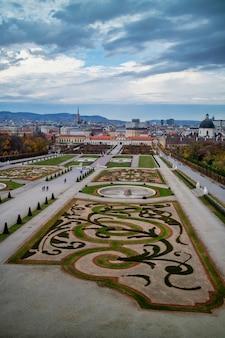 Piękny krajobraz kompleksu pałacowego schloss belvedere i parter ogrodowy z regularnym sadzeniem roślin i kwiatów w wiedniu, austria na tle zachmurzonego nieba.