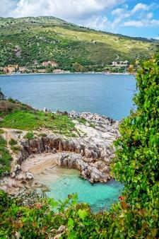 Piękny krajobraz - laguna morska z turkusową spokojną wodą, kamieniami i skałami na plaży, błękitne niebo, zielone drzewa i krzewy