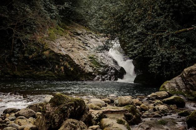Piękny krajobraz małego wodospadu do jeziora otoczonego skałami w łaźniach afrodyty w gruzji