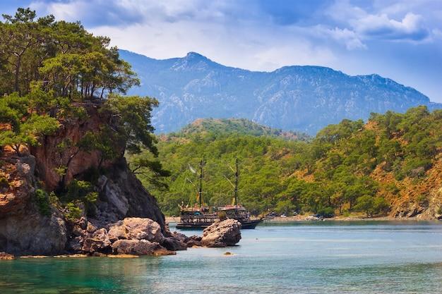 Piękny krajobraz morski. letni dzień w zatoce z górami i statkiem. indyk. antalya.