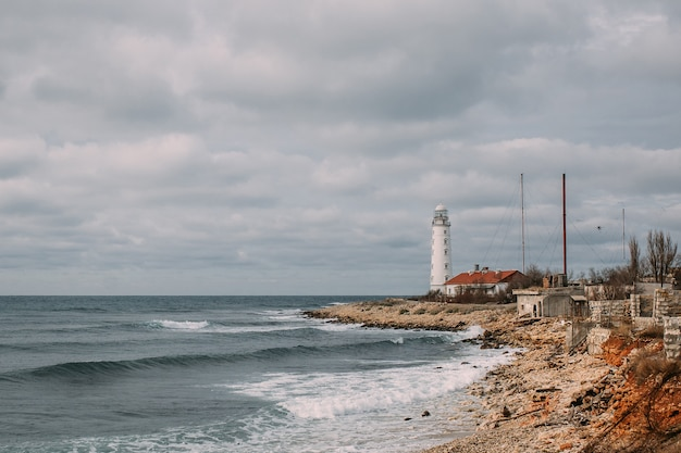 Piękny krajobraz morski z białą latarnią morską i starymi budynkami na brzegu. poniżej znajduje się falujące morze, a powyżej zachmurzone niebo