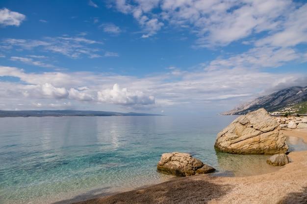 Piękny krajobraz morski z czystą wodą, górami i białymi chmurami w breli, chorwacji, riwierze makarskiej