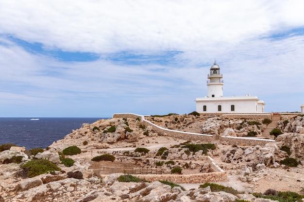 Piękny krajobraz morski z latarnią morską (faro de cavalleria) na klifie i statkiem wycieczkowym po morzu. minorka, baleary, hiszpania
