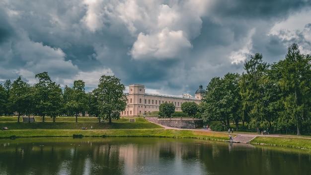 Piękny krajobraz parku ze stawem i wielkim pałacem gatchina. rosja