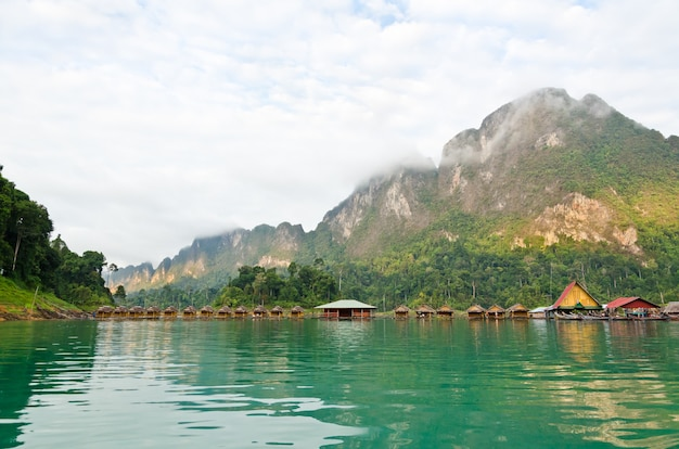 Piękny krajobraz przyrody zielonej góry i jeziora bambusa chata pływać w rząd stylu vintage country style w spokojny poranek, podróż do azji w parku narodowym khao sok, surat thani, tajlandia