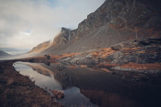 Piękny krajobraz skalistych klifów odbijający się w czystym strumieniu na islandii
