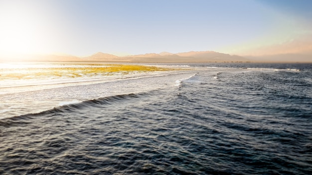 Piękny krajobraz spokojnego oceanu i gór na wybrzeżu. fale morskie toczące się i hamujące nad martwą rafą koralową i skałami o zachodzie słońca
