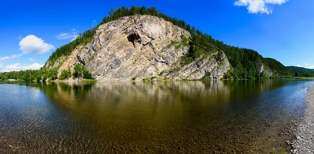 Piękny krajobraz spokojnej rzeki z nadmorskimi klifami i lasem iglastym, odbijający się w wodzie i atmosferycznym niebie