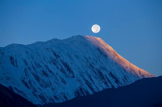 Piękny krajobraz w himalajach, region annapurna, nepal. księżyc w pełni podczas wschodu słońca na tle ośnieżonych gór