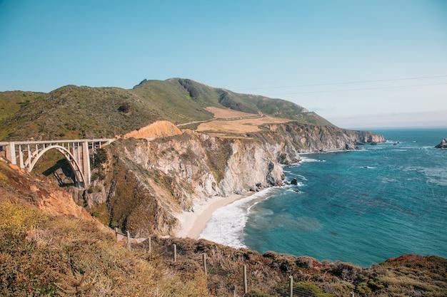 Piękny krajobraz w pobliżu miasta monterey w kalifornii. turkusowy ocean z dużymi falami i skalistymi klifami. rajska plaża kalifornii. ocean spokojny i klify z roślinami.