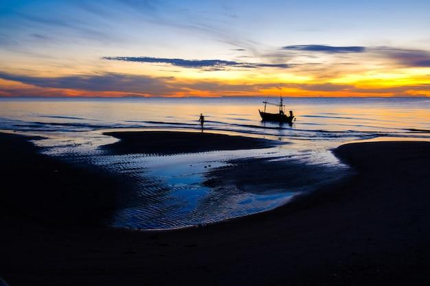 Piękny krajobraz widok przyrody w porannym wschodzie słońca z sylwetka łodzi rybackiej na plaży i pomarańczowe i błękitne niebo w tajlandii