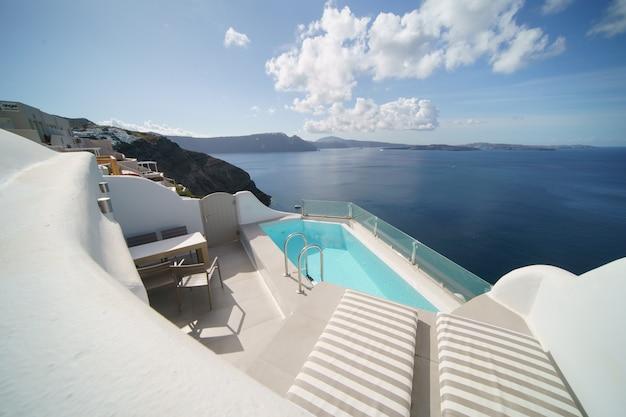 Piękny krajobraz willi z basenem z widokiem na morze, biała architektura na wyspie santorini, grecja.