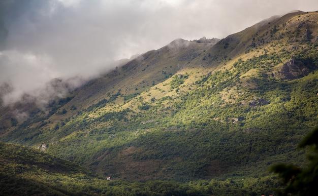Piękny krajobraz wysokich gór porośniętych trawą pokrytą chmurami