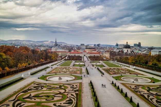 Piękny krajobraz z barokowym zespołem pałacowym schloss belvedere i parterem ogrodowym z regularnym sadzeniem roślin i kwiatów w wiedniu, austria na tle zachmurzonego nieba.