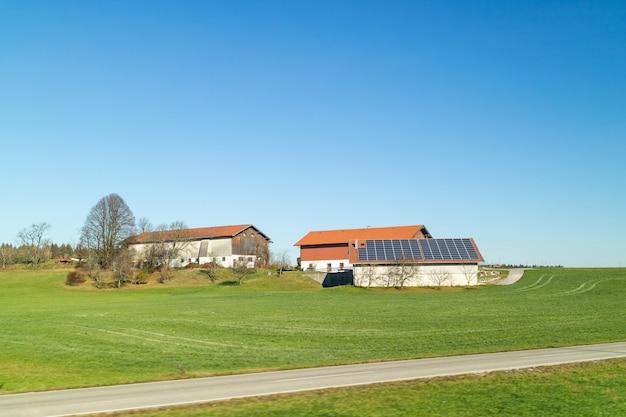 Piękny krajobraz z budynkami rolniczymi z panelami słonecznymi na dachu na zielonych polach i terenach na tle błękitnego czystego nieba jesienią, austria.