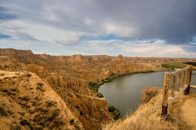 Piękny krajobraz z czerwonymi skałami i jeziorem w barrancas de burujon, toledo, hiszpania