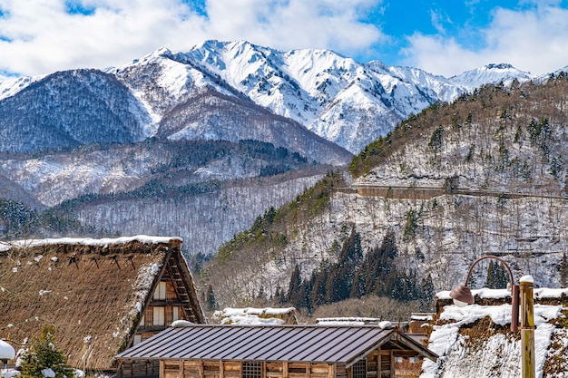 Piękny krajobraz z dachami wiosek, sosnami i ośnieżonymi górami w japonii