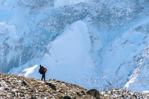 Piękny krajobraz z górami, niebieskim ogromnym lodowcem i sylwetką spacerującego mężczyzny z dużym plecakiem i gitarą
