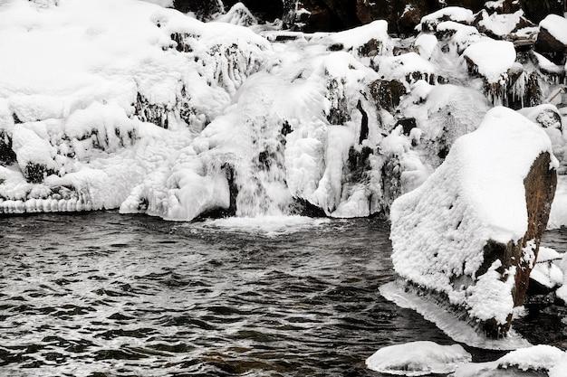 Piękny krajobraz z górskim strumieniem i wodospadem w zimowy dzień