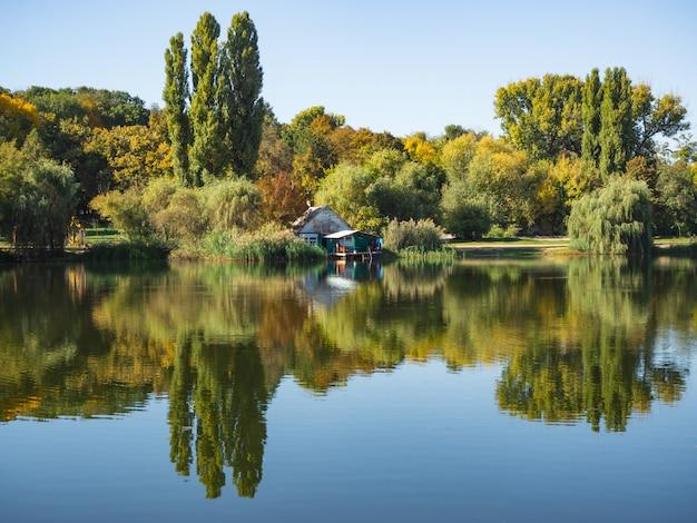 Piękny krajobraz z małym domkiem nad jeziorem.