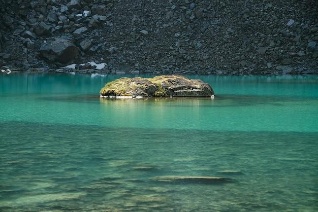 Piękny krajobraz z omszałą skałą w turkusowym górskim jeziorze z przezroczystą wodą i kamienistym dnem. lazurowe jezioro polodowcowe w słońcu. kolorowa sceneria z omszałym kamieniem nad czystą wodą.