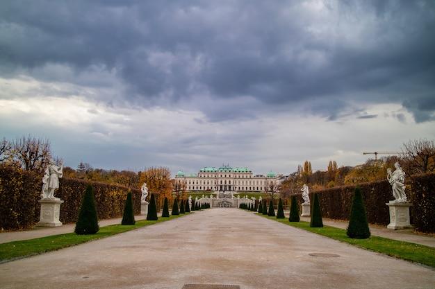 Piękny krajobraz z szeroką główną aleją spacerową przed schloss belvedere palace z regularnym sadzeniem drzew i starożytnych posągów w wiedniu, austria na tle zachmurzonego nieba.