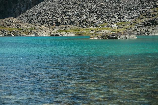 Piękny krajobraz z turkusowym górskim jeziorem. lazurowe jezioro polodowcowe w słońcu. kolorowa słoneczna sceneria z czystą wodą tafli górskiego jeziora. jezioro lodowcowe z przejrzystą wodą i kamienistym dnem