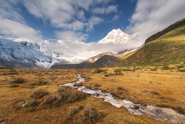 Piękny krajobraz z wysokimi górami z ośnieżonymi szczytami, małą rzeką, żółtą trawą i pochmurnym niebem przy kolorowym wschodem słońca.