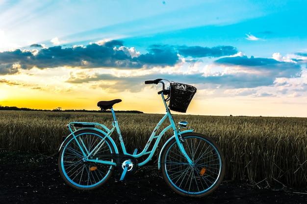 Piękny krajobraz z zabytkowym rowerem o zachodzie słońca