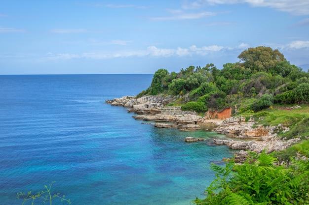 Piękny krajobraz z zatoką morską z turkusową wodą, skałami i klifami, zielonymi drzewami i krzewami. wyspa korfu, grecja.