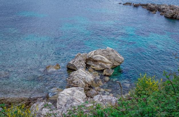 Piękny krajobraz z zatoką morską z turkusową wodą, skałami i klifami, zielonymi drzewami i krzewami
