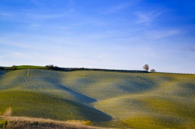 Piękny krajobraz zielonych wzgórz pod jasnym, błękitnym niebem