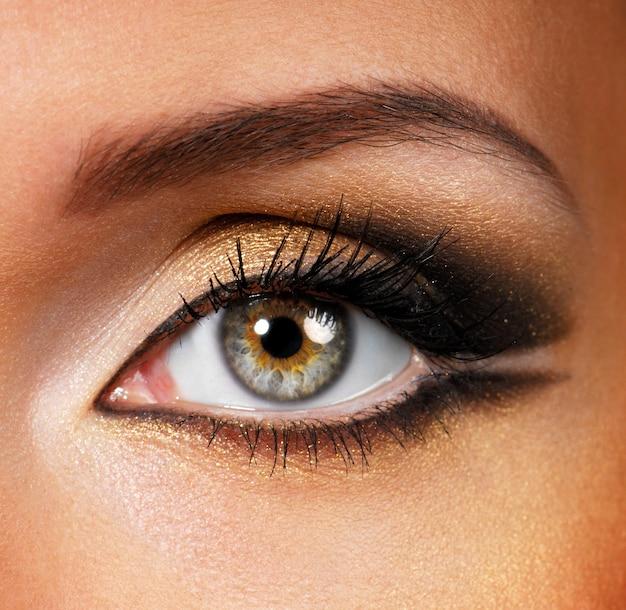 Piękny kształt kobiecego oka ze złotobrązowym makijażem kosmetycznym