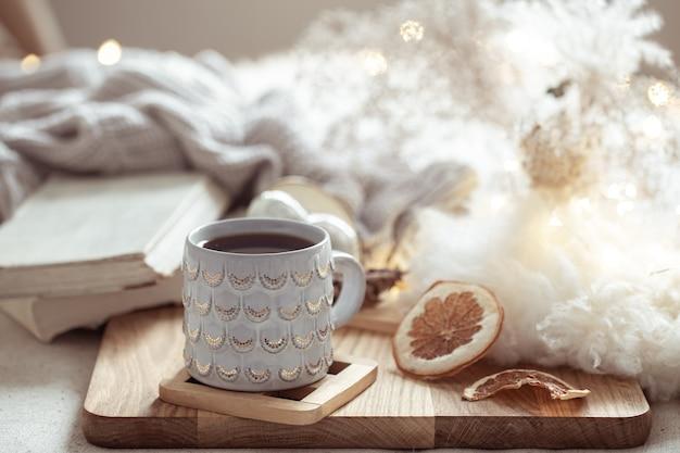 Piękny kubek z gorącym napojem na tle przytulnych rzeczy. koncepcja komfortu i ciepła w domu.