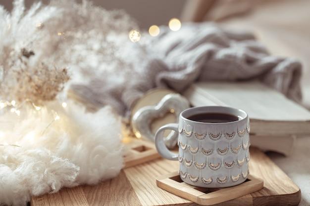 Piękny kubek z gorącym napojem w przestrzeni przytulnych rzeczy. koncepcja komfortu i ciepła w domu.