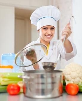 Piękny kucharz w toque przygotowuje wegetariański lunch