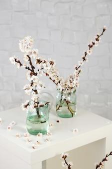 Piękny kwiat moreli w przezroczystych słoikach na szarym tle ściany