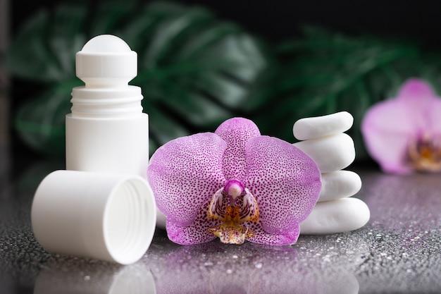 Piękny kwiat orchidei bzu i biały dezodorant w kulce z białymi kamieniami i liśćmi monstery