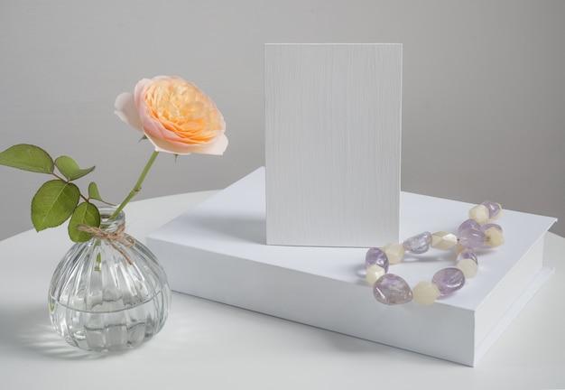 Piękny kwiat róży w szklanym wazonie z zaproszeniem i dekoracją białej książki na białej powierzchni stołu