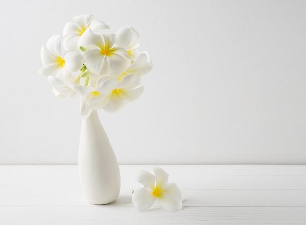 Piękny kwiat spa frangipani w nowoczesnym ceramicznym białym wazonie na drewnianej powierzchni białej ściany z miejscem na kopię