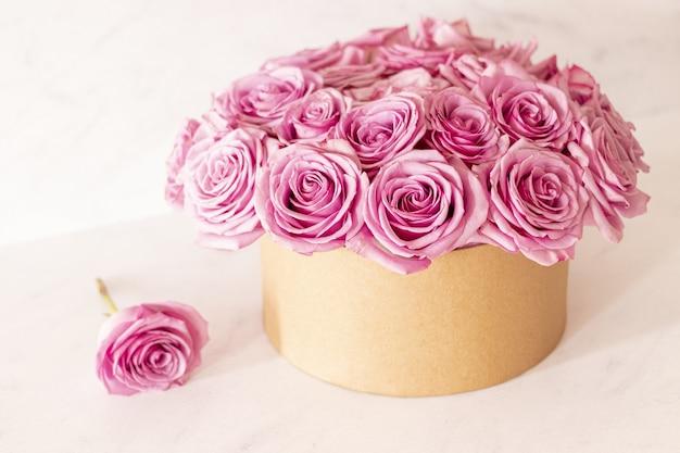 Piękny kwiatowy bukiet z różowymi różami w pudełku na różowym tle