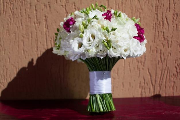 Piękny, kwitnący bukiet pastelowych różowych róż ze wstążką