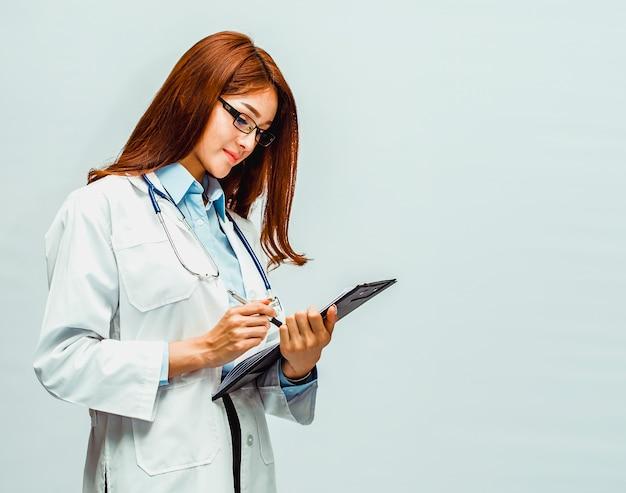 Piękny lekarz pisze zapis wyników badania pacjenta