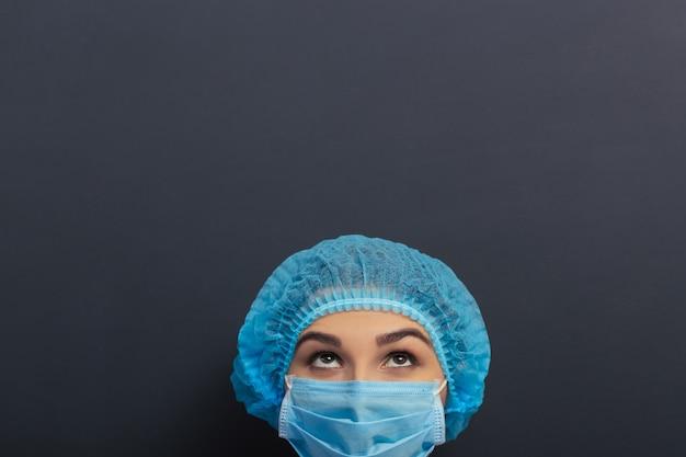 Piękny lekarz w białej sukni, czapce i masce medycznej.